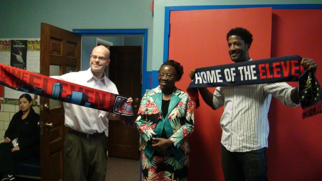 Indy Eleven staff members John Koluder and Guy-Jo Gordon present team scarves to the Madame Minister Lukenge who visited Indiana to, among other things, meet with people involved in the WAZA Alliance educational outreach efforts in the D.R. Congo. (Photo by R. Townsend)